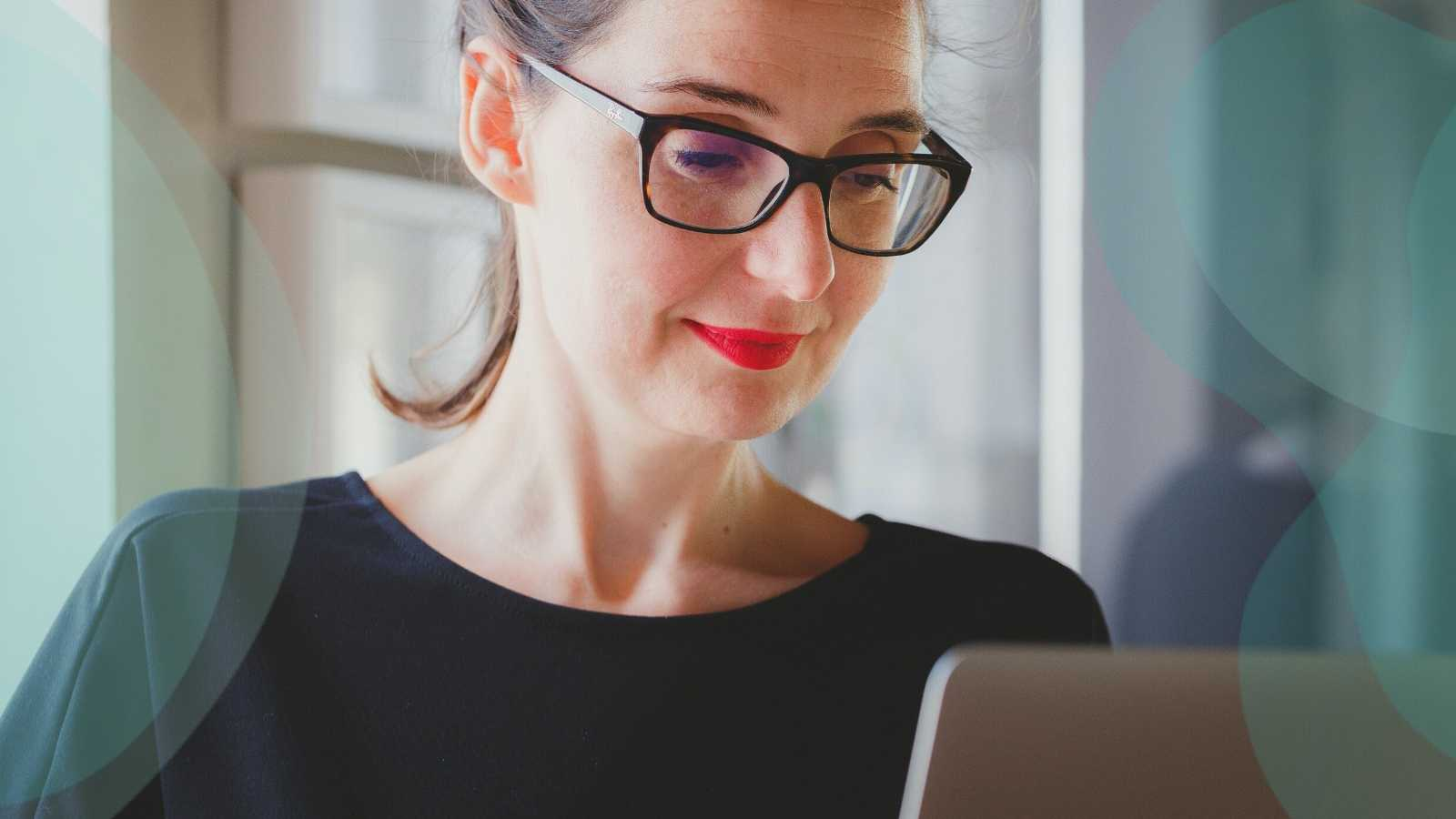 Woman with a kind face typing on her laptop. She is wearing thick-rimmed glasses and red lipstick.