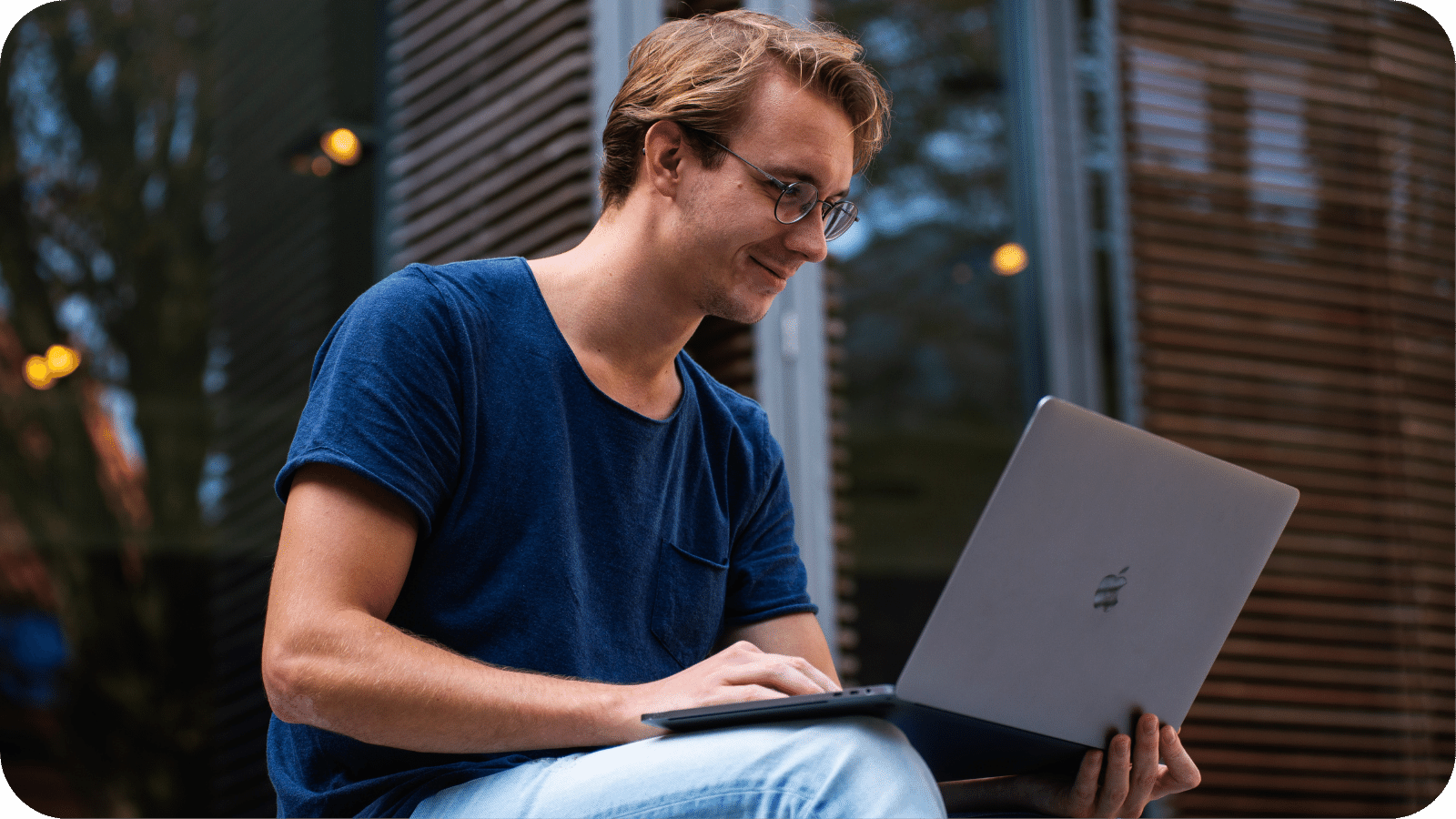 A man using a laptop while sitting casually outdoors